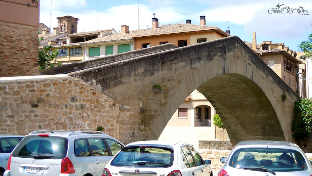 Photo of stone bridge, patchy blue sky, cars in front, Puente Picudo, Estella, Spain
